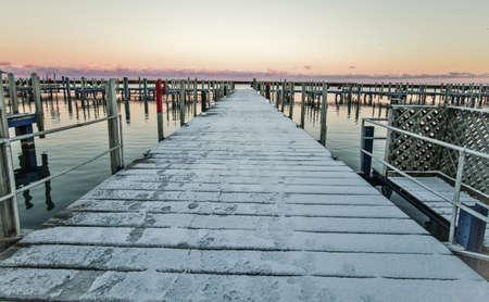 settles: Abandoned Winter Harbor. Snow covers an empty harbor and marina as winter settles in over the coast of Lake Huron.