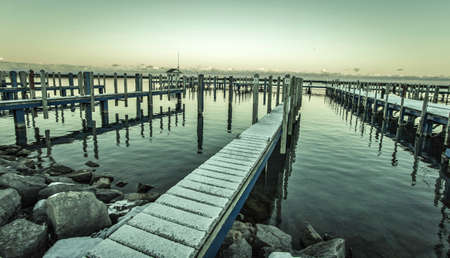 settles: Lake Huron Gray. Snow falls on an abandoned marina as winter settles in over the coast of Lake Huron. Stock Photo