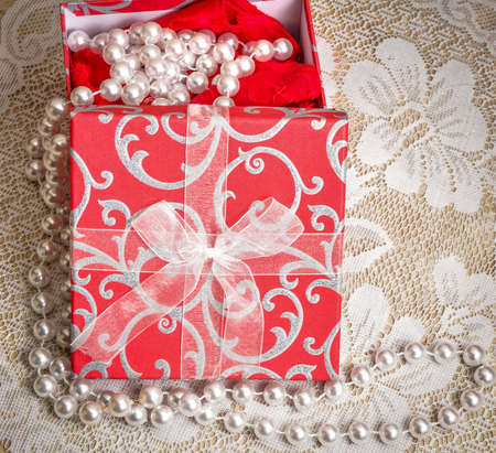 anniversary sexy: Romantic Sexy Gift. A red and white gift box with pearls and a red nightie on a lace background in square orientation