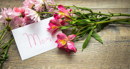 text message: Mothers Day Card With A Bouquet. Envelope with handwritten label and a bouquet of fresh flowers in panoramic orientation.