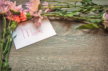felicitaciones cumplea�os: Mothers Day Bouquet And Card. Fresh bouquet of daisy, iris and carnations with a handwritten card labeled Mom. Shot from above on a rustic wooden background with copy space.