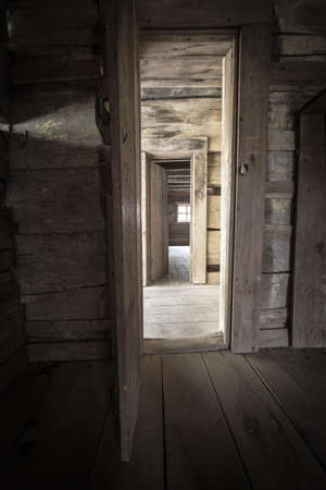 not open: Hallway With Open Doors And Sunlight. Abandoned cabin with hallway and open doors encased in light. This is a historical structure in a national park and not a private residence. Stock Photo