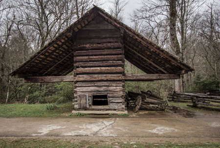 covered wagon: Agriculture Vintage Style Background. Pioneer corn crib and covered wagon outside a historical 18th century outbuilding. This is a public owned building in a national park and not a privately owned residence.