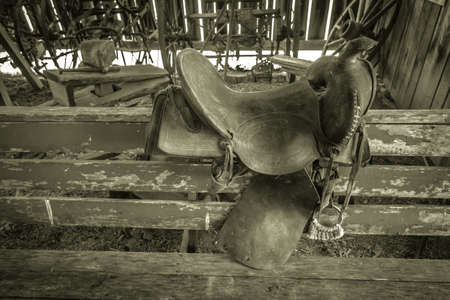 western saddle: Antique Western Saddle. Black and white interior of a barn and saddle on the fence.