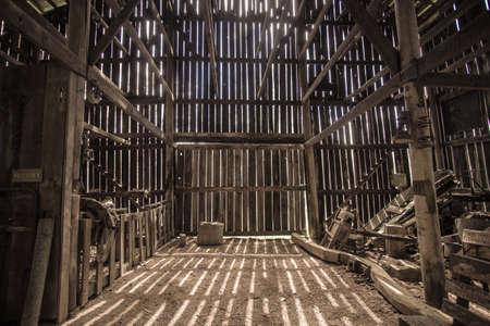 Luz de la mañana ilumina Barn interior. sol de la mañana ilumina el interior de un granero iluminando maquinaria agrícola de época y una silla de montar. Este es un granero abierto al público en las tierras del parque público, no es una propiedad privada. Foto de archivo