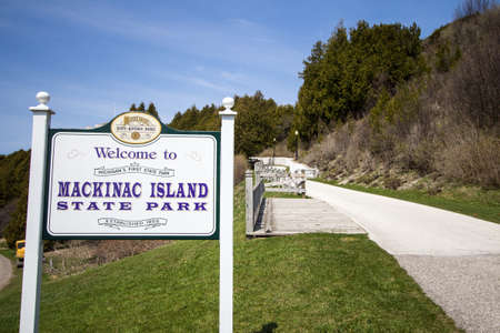 encompasses: Mackinac Island, Michigan, USA - May 6, 2016 - Welcome and paved trail in Mackinac  signIsland State Park. The park encompasses over 74% of the island and was Michigans first state park.