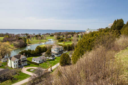 mackinac: Mackinaw Island, Michigan, USA - May 6, 2016: Panorama overlook of the city of Mackinaw Island with the Grand Hotel and golf course at the horizon.