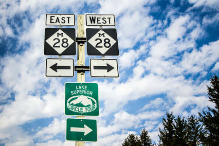 marquette: Munising, Michigan, USA - May 7, 2016: Highway M-28 travels east west through Michigans Upper Peninsula along the shores of Lake Superior. It is a major thoroughfare for tourists and residents throughout Marquette, Sault Ste. Marie and Newberry.