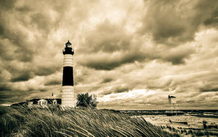 ludington: Stormy Vintage Great Lakes Lighthouse Coast. Stormy horizon and the windswept coast of Lake Michigan with the Big Sable Lighthouse. Ludington State Park.