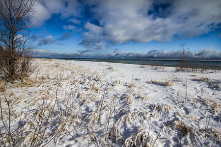 michigan snow: Michigan Winter Beach Landscape Or Background. Frozen beach with the open waters of Lake Huron at the horizon under a sunny blue sky. Horizontal orientation with copy space in the foreground.