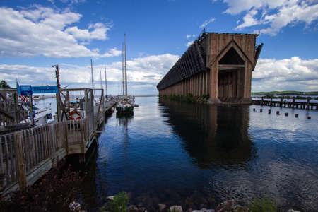 marquette: Marquette, Michigan, USA - June 21, 2016: Marquette harbor and marina with historic iron ore dock in the background.