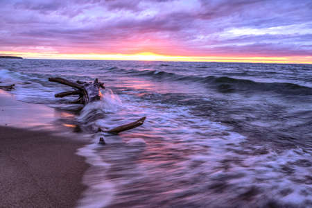 sea monster: Driftwood Beach. Driftwood abstract resembling a sea monster surrounded  by waves set against a sunset sky. Port Crescent State Park. Port Austin, Michigan.