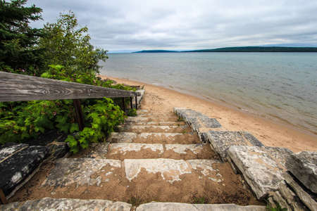 Stairs To A Beautiful Sandy Beach In Michigan. Winding stone stairs lead to a sandy beach on the shores of Lake Superior in Michigan's Upper Peninsula. Hiawatha National Forest. Munising, Michigan.