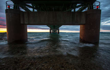 mackinac: Under The Mackinaw Bridge in Michigan. Sunset horizon from the underneath the mighty Mackinac Bridge in Michigan. The Mackinaw Bridge is one of the longest suspension bridges in the world and connects the Upper and Lower Peninsulas of Michigan. Stock Photo