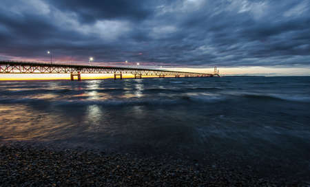 mackinac: Dramatic Sky Over The Mackinac Bridge. Clouds and sunset sky over the Mackinac Bridge. Located in Michigan, it is the longest suspension bridge in the Western Hemisphere and connects the Upper and Lower Peninsula.