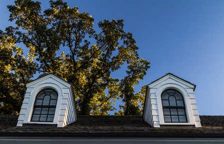 Koekoeken Op Een Zwarte Shingle Roof. Dubbele dakkapellen op een zwarte dakspaandak met witte gevelbeplating en zwarte versiering.