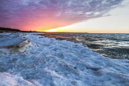 Winter Coast Great Lakes Background. Snow and ice on the Great Lakes on a cold winter day with a sunset background. Port Crescent State Park. Port Austin, Michigan.