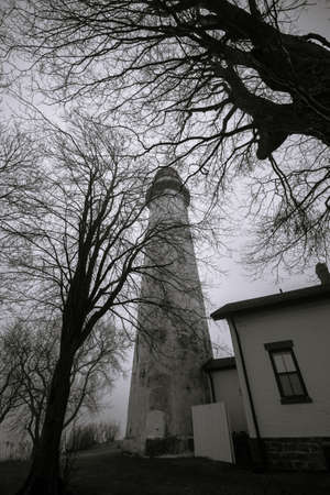 reportedly: Haunted Great Lakes Michigan Lighthouse. The reportedly haunted Pt. Aux Barques Lighthouse on the remote shores of Lake Huron surrounded by bare trees in vertical orientation. Port Hope, Michigan.