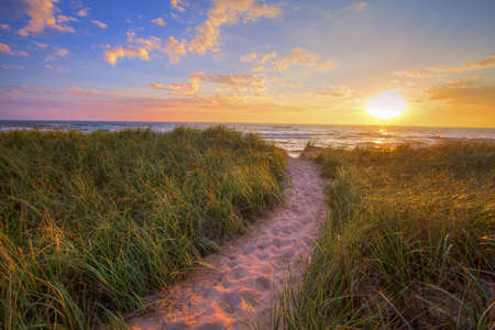 Path To A Sunset Beach. Winding trail through dune grass leads to a sunset beach on the coast of the inland sea of Lake Michigan. Hoffmaster State Park. Muskegon, Michigan. 免版税图像