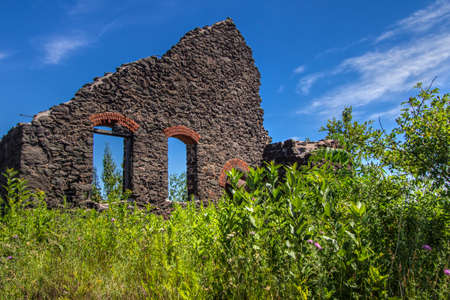 Abandoned Ghost Town Building. Exterior of a crumbling sandstone building reminiscent of a wild west ghost town. The building is located on a an abandoned mine site in the Keweenaw National Historic Park in Calumet, Michigan. Stock Photo