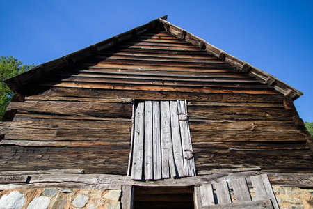 Pioneer Style Wooden Barn. 1800s pioneer barn front with loft door. Structure is historical property in a national park and not private property. Stock Photo