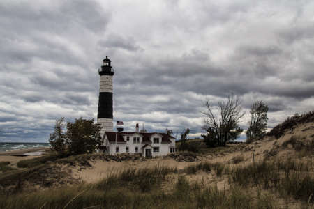 thunderhead: Storm On The Horizon. Dark storm clouds surround the Big Sable Point Lighthouse on the remote shores of Lake Michigan in Ludington State Park in Michigans Lower Peninsula.