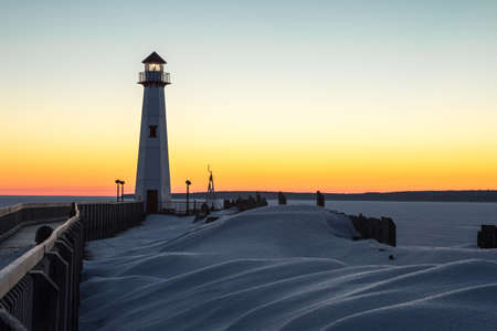 Winter Coastal Sunrise. Winter sunrise on the frozen shores of the Great Lakes with Wawatam Lighthouse in the St. Ignace harbor in Michigans Upper Peninsula Stock Photo