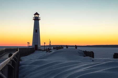 Winter kust zonsopgang. De winterzonsopgang op de bevroren kusten van de Grote Meren met Wawatam-Vuurtoren in de St Ignace-haven in het Hogere Schiereiland van Michigan Stockfoto