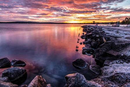 Downtown Traverse City Coastal Sunrise. Morning sunrise over the rocky coast of Grand Traverse Bay with downtown Traverse City, Michigan in the background. Фото со стока - 89135967