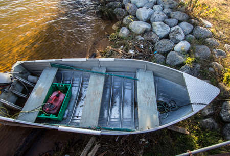 Small Fishing Boat On The Shore. Small aluminum rowboat with gas motor on the Great Lakes shore. Shot from above in horizontal orientation. 版權商用圖片