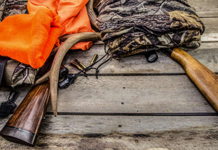 Fondo de caza del ciervo. Caza rifles, alcance, astas, balas y ropa de caza en un fondo de madera rústica con espacio de copia. Foto de archivo