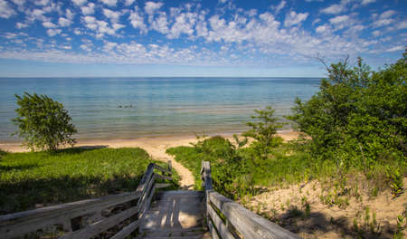 Sunny Summer Beach Background. Stairs lead to a beautiful sandy beach with crystal clear blue water and a sunny summer blue sky at the horizon. Northern shore of Lake Michigan in the Upper Peninsula. Stock Photo