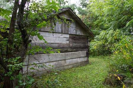Behind The Wooden Shed. Old weathered rural wood shed in the American Midwest. Stock fotó