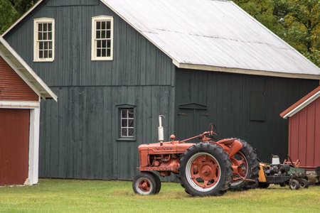 Farming Background. Red antique tractor and traditional barn in the American Midwest Imagens