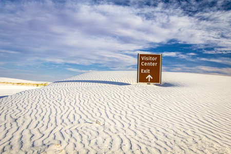 Abstrait du désert. Panneau de sortie du centre d'accueil dépassé par le vent et le sable au White Sands National Monument dans les déserts du sud-ouest américain du Nouveau-Mexique.