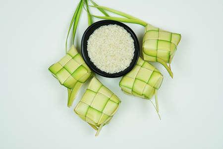 Ketupat大米外壳由年轻的椰子叶为烹饪大米在白色的背景。黑碗里的米饭。孤立的白色bckground。有选择性的重点。