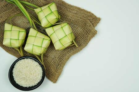 Boyau de riz ketupat fabriqué à partir de jeunes feuilles de coco pour la cuisson du riz sur fond blanc. Riz dans un bol noir. Fond blanc isolé. Mise au point sélective.