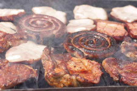barbecuing: Barbecuing minced meat, traditional Romanian preparation for barbecue, called mici,  on charcoal fire - closeup image.