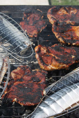 barbecuing: Barbecuing mackerel and red meat on charcoal fire closeup image.