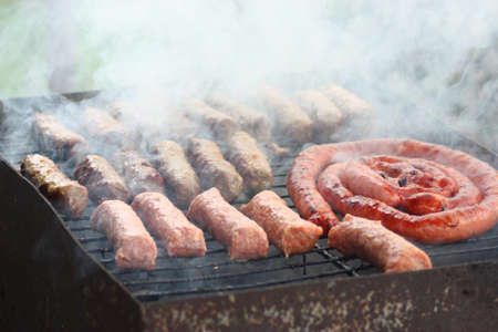 barbecuing: Barbecuing meat on charcoal fire closeup image. Stock Photo