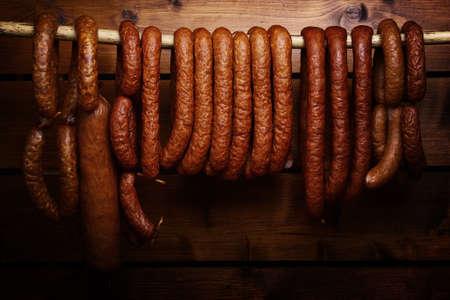 slaughter: Sausage hanged on dark wooden background