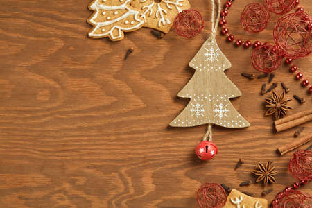 joyeux: Christmas gingerbread on wooden background with various decoration and spices