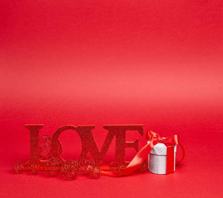 Red background with big glitter love sign and gift