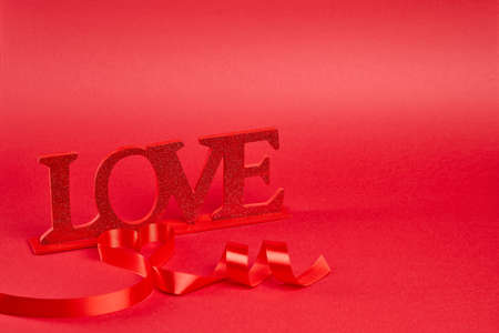 Red background with big glitter love sign with ribbon curled into heart and message Stock Photo