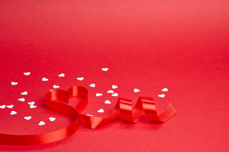 Red background with ribbon curled into heart and white confetti