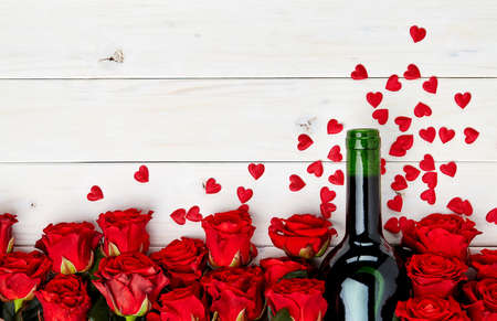 Buds of red roses and bottle of wine on a white wooden background with confetti Stock Photo