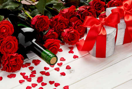 Buds of red roses and bottle of wine on a white wooden background with confetti and gift Stock Photo