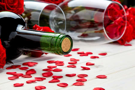 Buds of red roses and bottle of wine on a white wooden background with confetti and glass