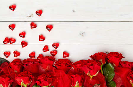 crystal heart: Buds of red roses on white wooden background crystal heart confetti