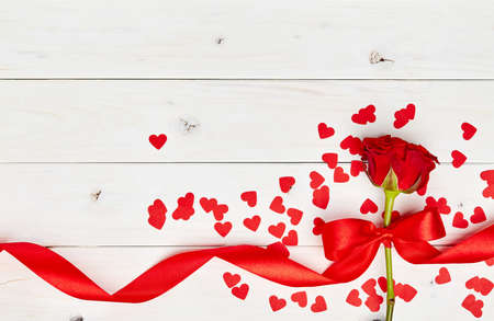 Single red rose on a white wooden background with ribbon and confetti hearts